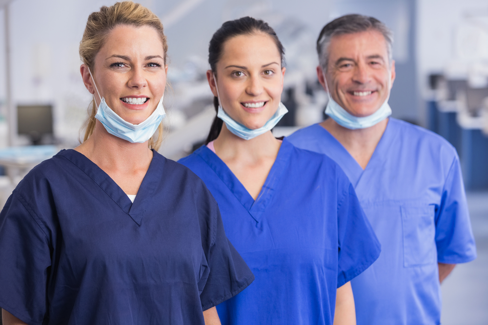 Portrait of smiling co-workers standing in a line in dental clinic